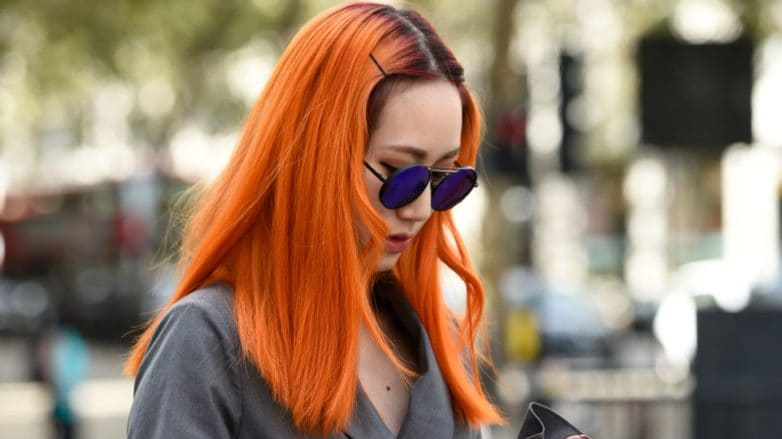 Woman wearing grey jacket with long orange hair, holding phone and posing on the street