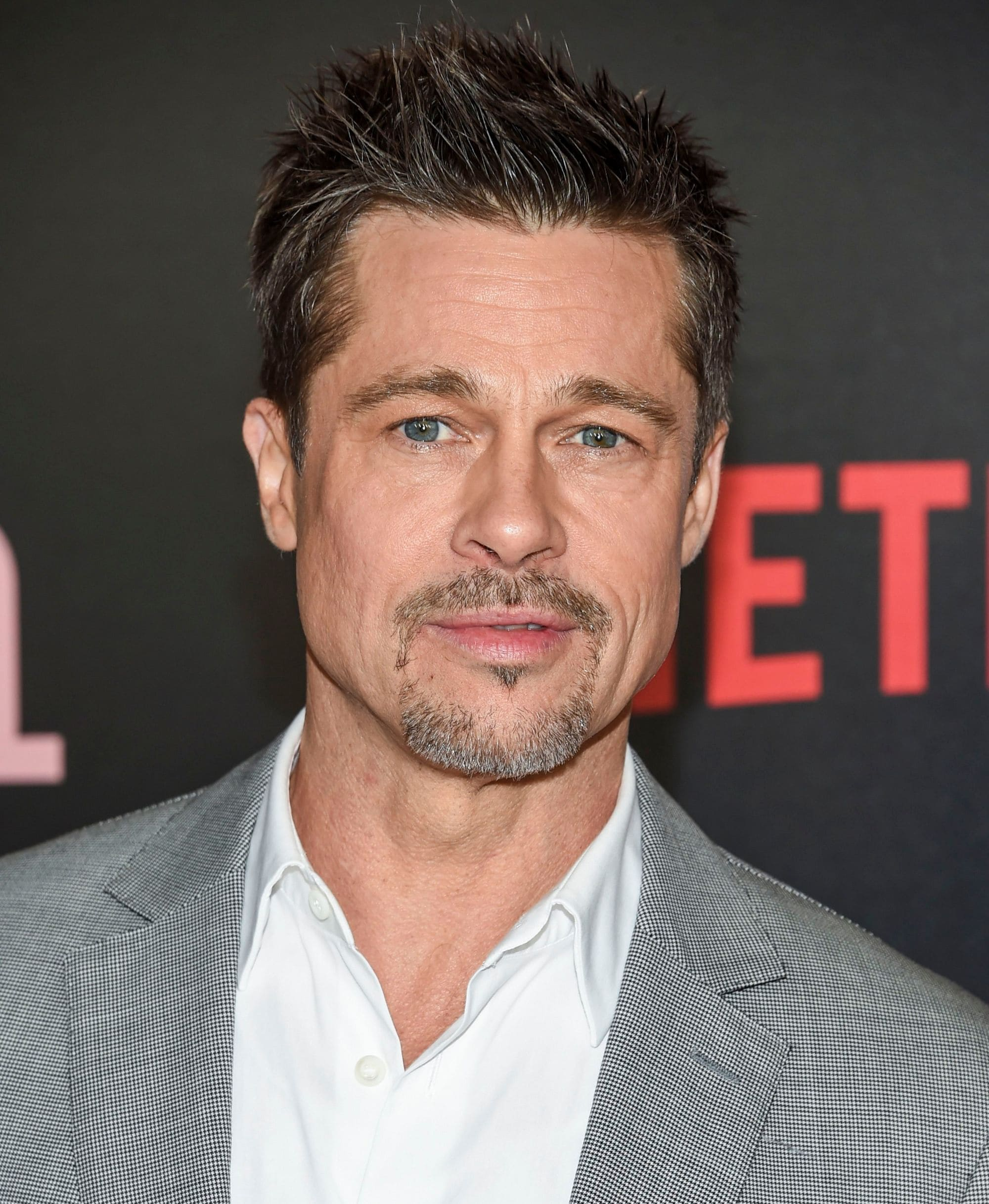 Hairstyles for men over 50: Brad Pitt with short spiky dark blonde hair and stubble beard wearing a grey and white suit at film premiere.