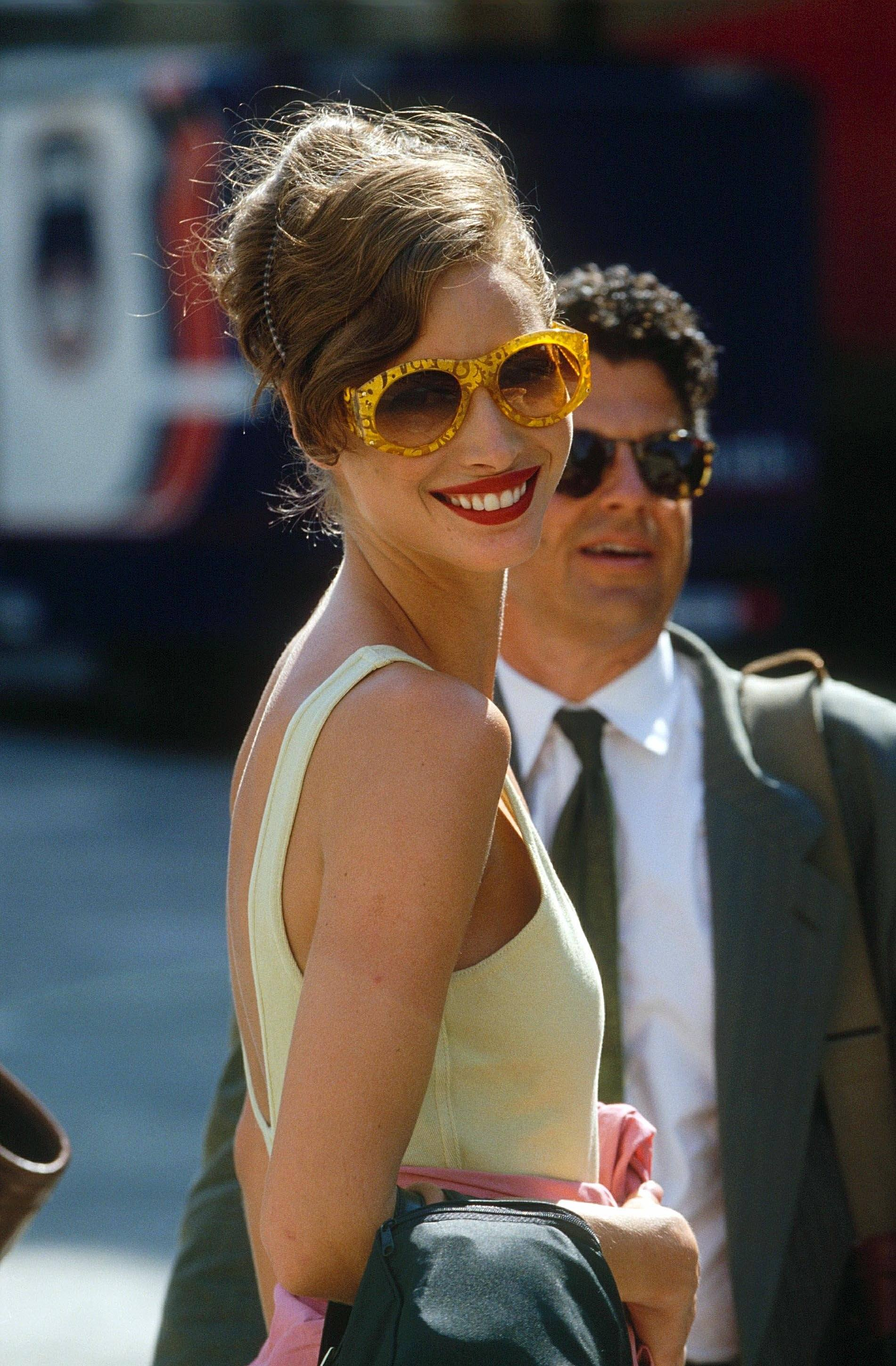 Christy Turlington with brown hair in side parted updo wearing yellow sunglasses and yellow dress.