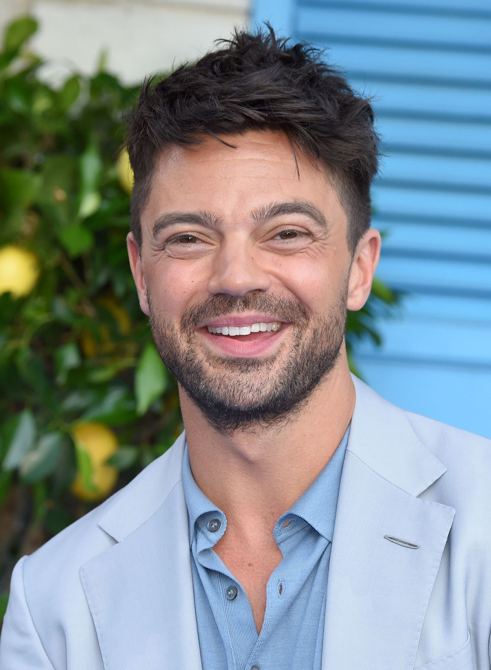 Hairstyles for men over 40: Close-up of Dominic Cooper with brown choppy textured hair, smiling at the camera
