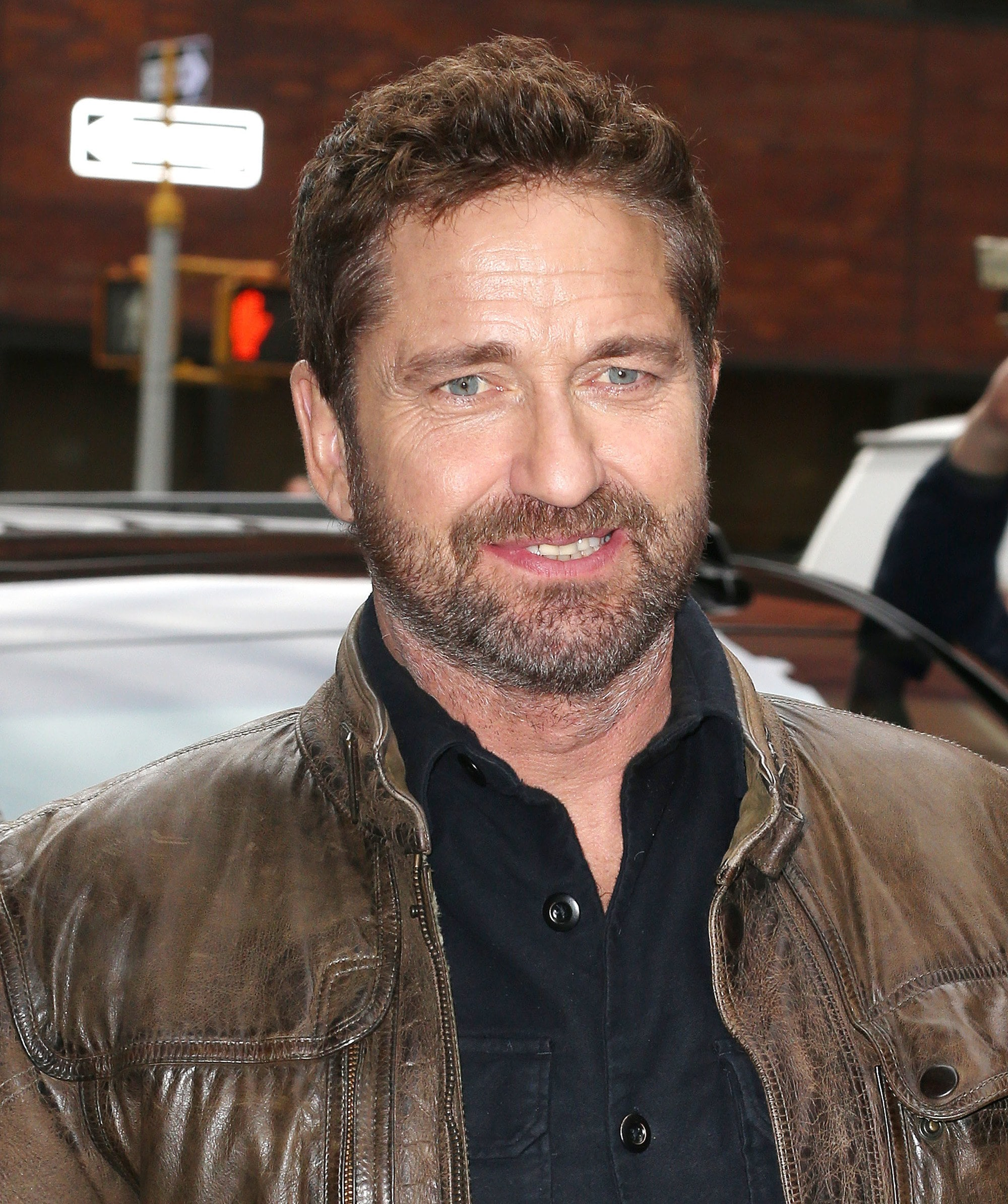 Hairstyles for men over 40: Gerard Butler with short curly brown hair and stubbly facial hair,wearing a shirt and a brown leather jacket