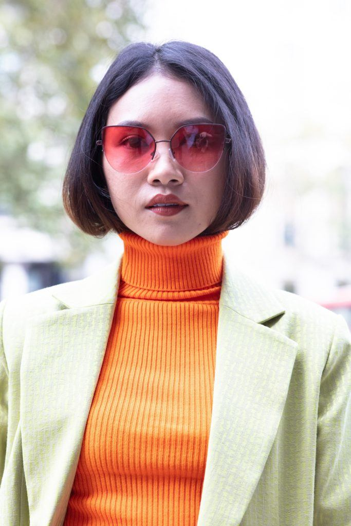 Turtleneck hair ideas: Woman with chocolate brown hair tucked into her orange turtleneck top, wearing mint blazer with sunglasses outside
