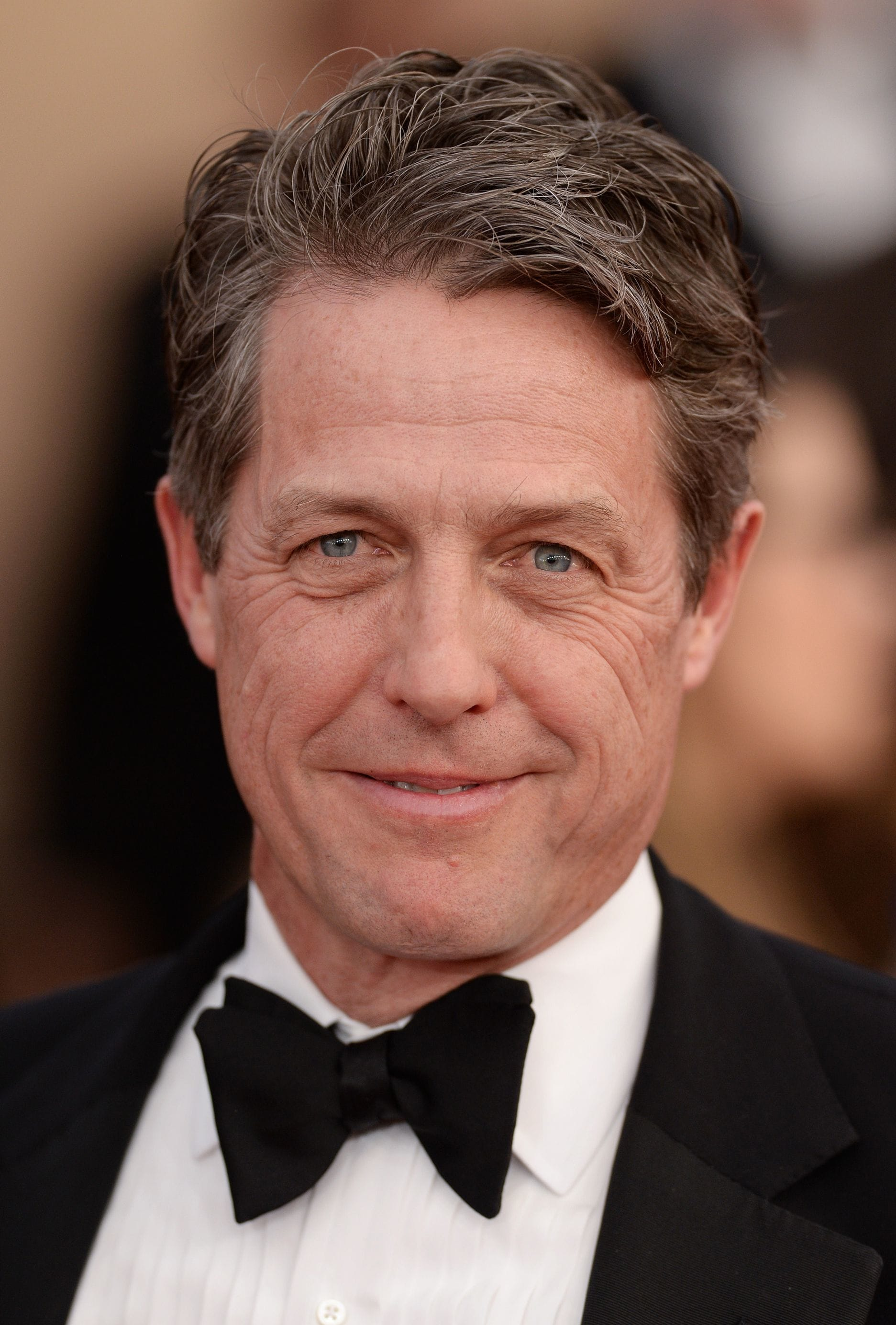 Hairstyles for men over 50: Hugh Grant with light brown textured short hair wearing a formal suit at event.