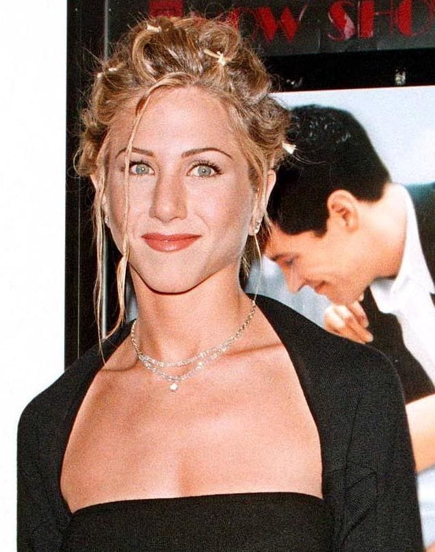 Jennifer Aniston with golden blonde highlighted hair in updo with butterfly clips in the '90s.