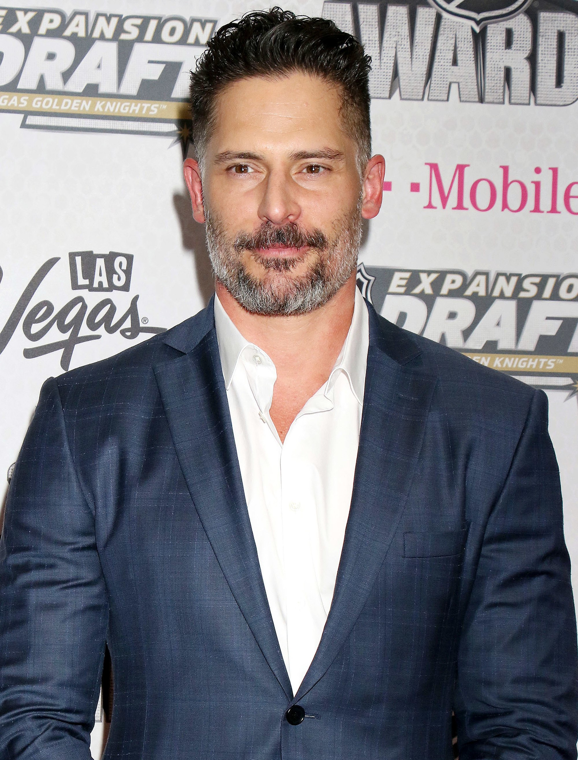 Hairstyles for men over 40: Photo of Joe Manganiello with gelled up brown hair and grey facial hair, wearing a white shirt and blue suit jacket