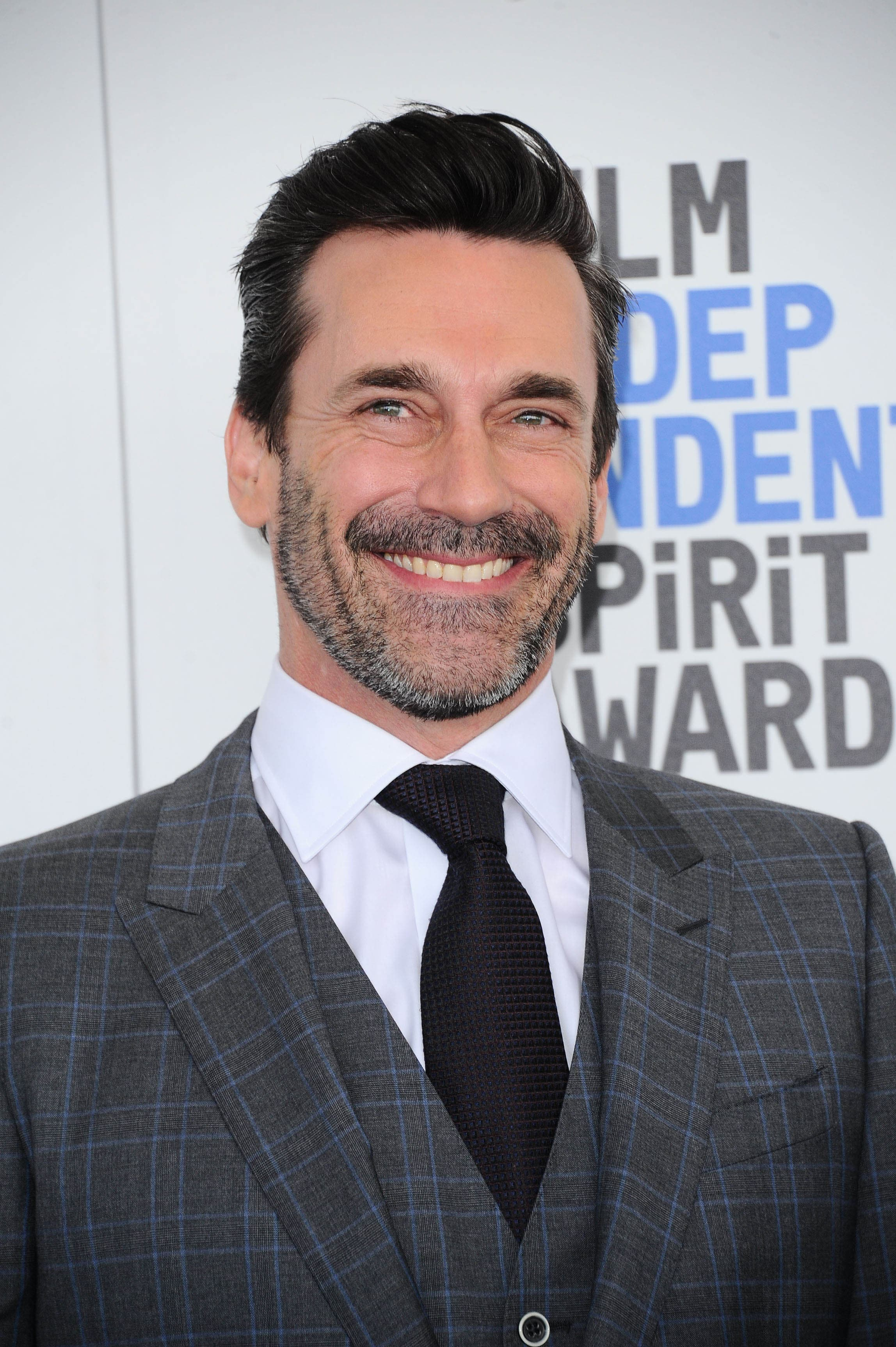 Hairstyles for men over 40: Photo of John Hamm with dark brown swept back hair and stubble