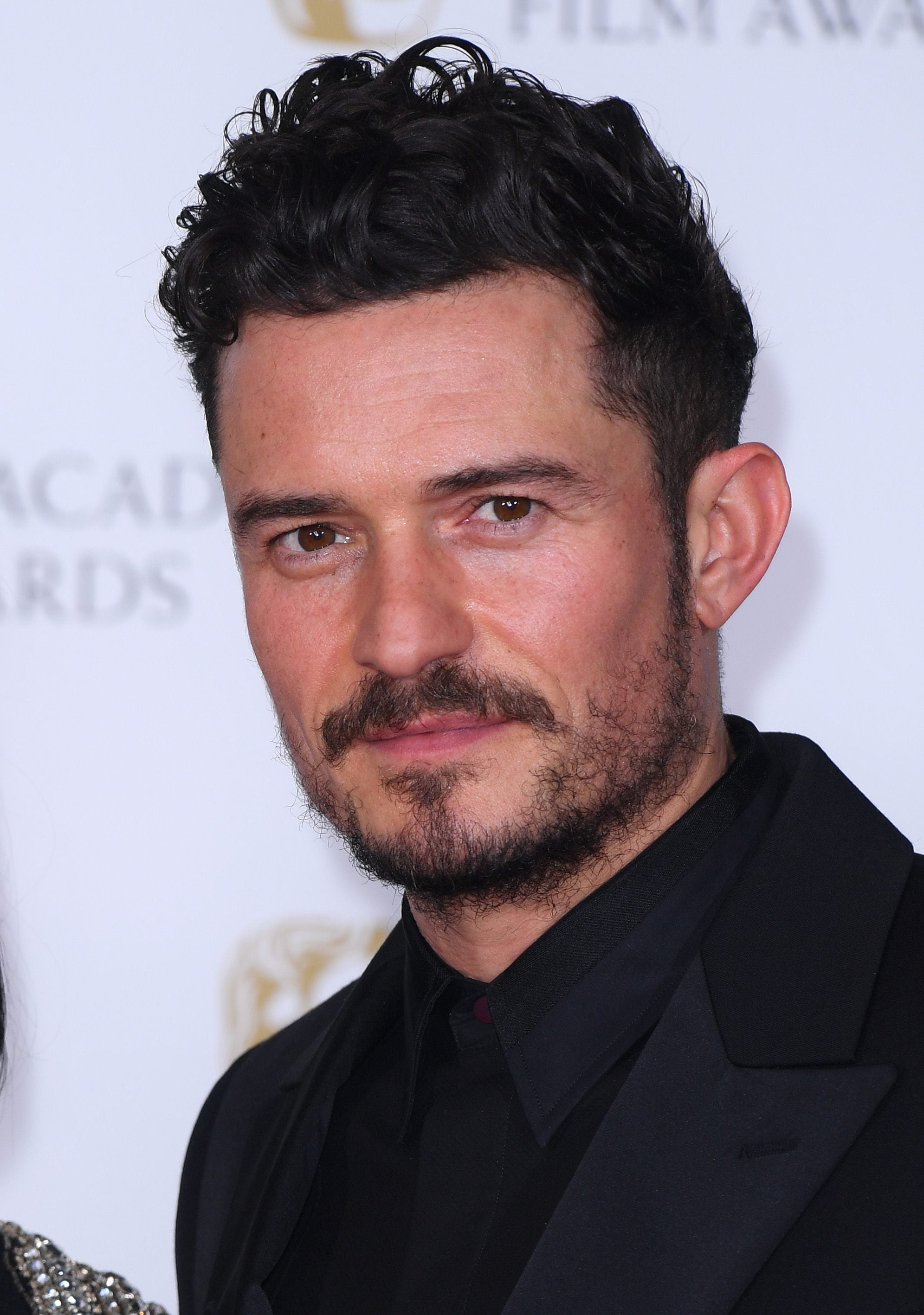 Hairstyles for men over 40: Close-up of Orlando Bloom with curly tousled dark brown short hair