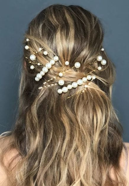 Party hair accessories: Woman with highlighted blonde wavy hair styled in a half-up, half-down style adorned with pearl hair accessories.