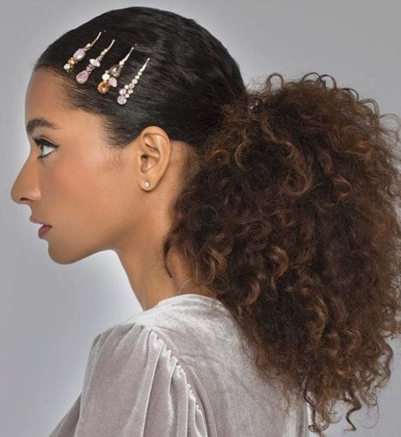 Party hair accessories: Model with brown naturally curly hair in smooth low ponytail with crystal hair slides along the front of hair.