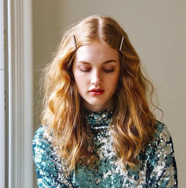 Party hair accessories: Woman with long wavy strawberry blonde hair with hair slides at the temple wearing a sequin top.