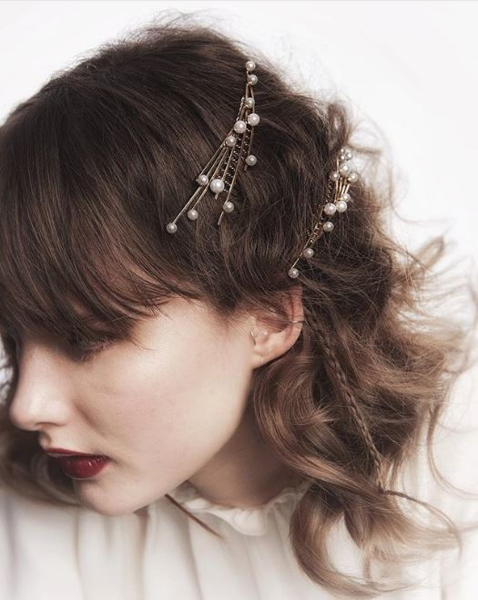 Party hair accessories: Woman with brown wavy shoulder length hair with pearl hair pins along the side.