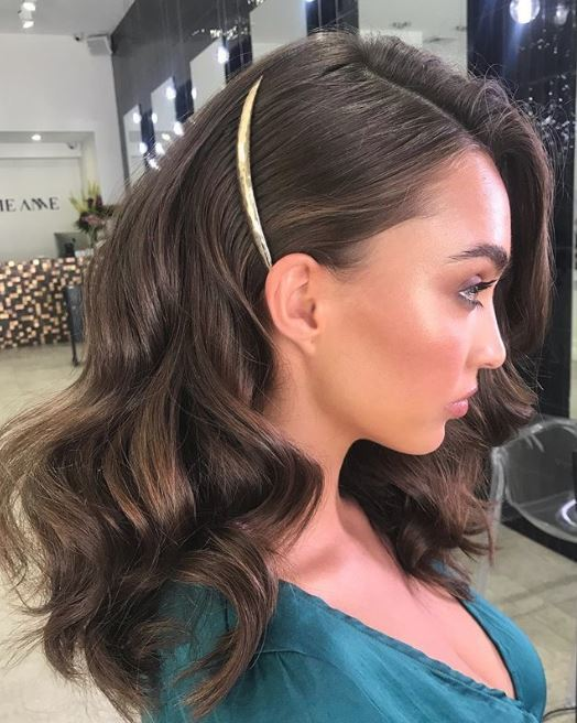 Party hair accessories: Woman with large bouncy waves on medium length brunette hair with a single gold hair slide pinning the side back.