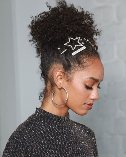 Party hair accessories: Woman with naturally curly brown hair in high ponytail with jewelled hair pins and slides along the front of the hair.