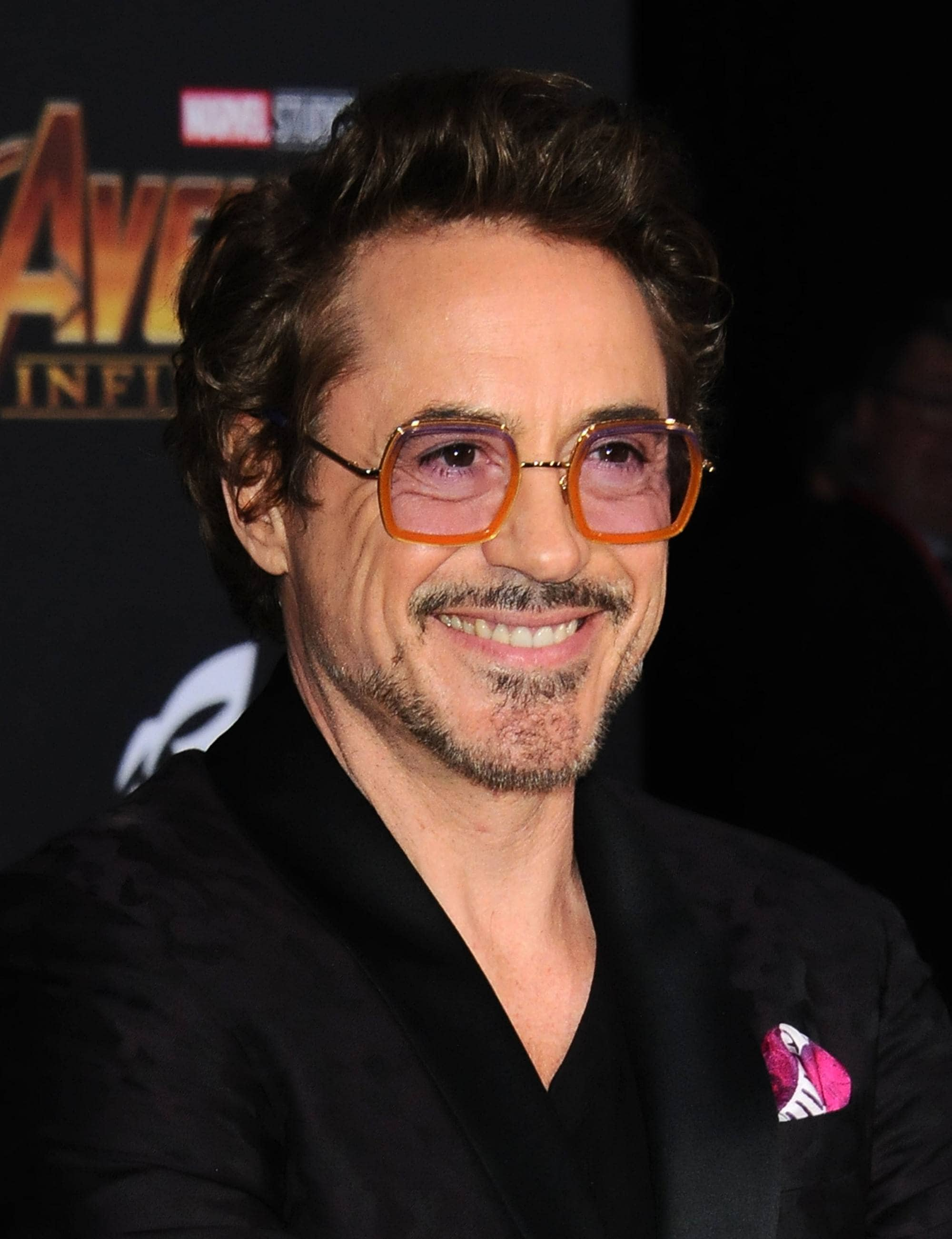 Hairstyles for men over 50: Robert Downey Jr with brown swept back short quiff hair with stubble beard and bold glasses wearing a suit at the Avengers premiere.