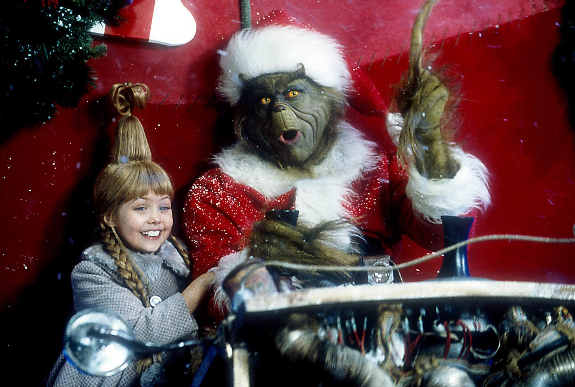 The Grinch: Taylor Momsen as Cindy Lou Who with her hair golden blonde hair styled into braided pigtails, wearing grey winter outfit, posing in the sleigh with The Grinch on set