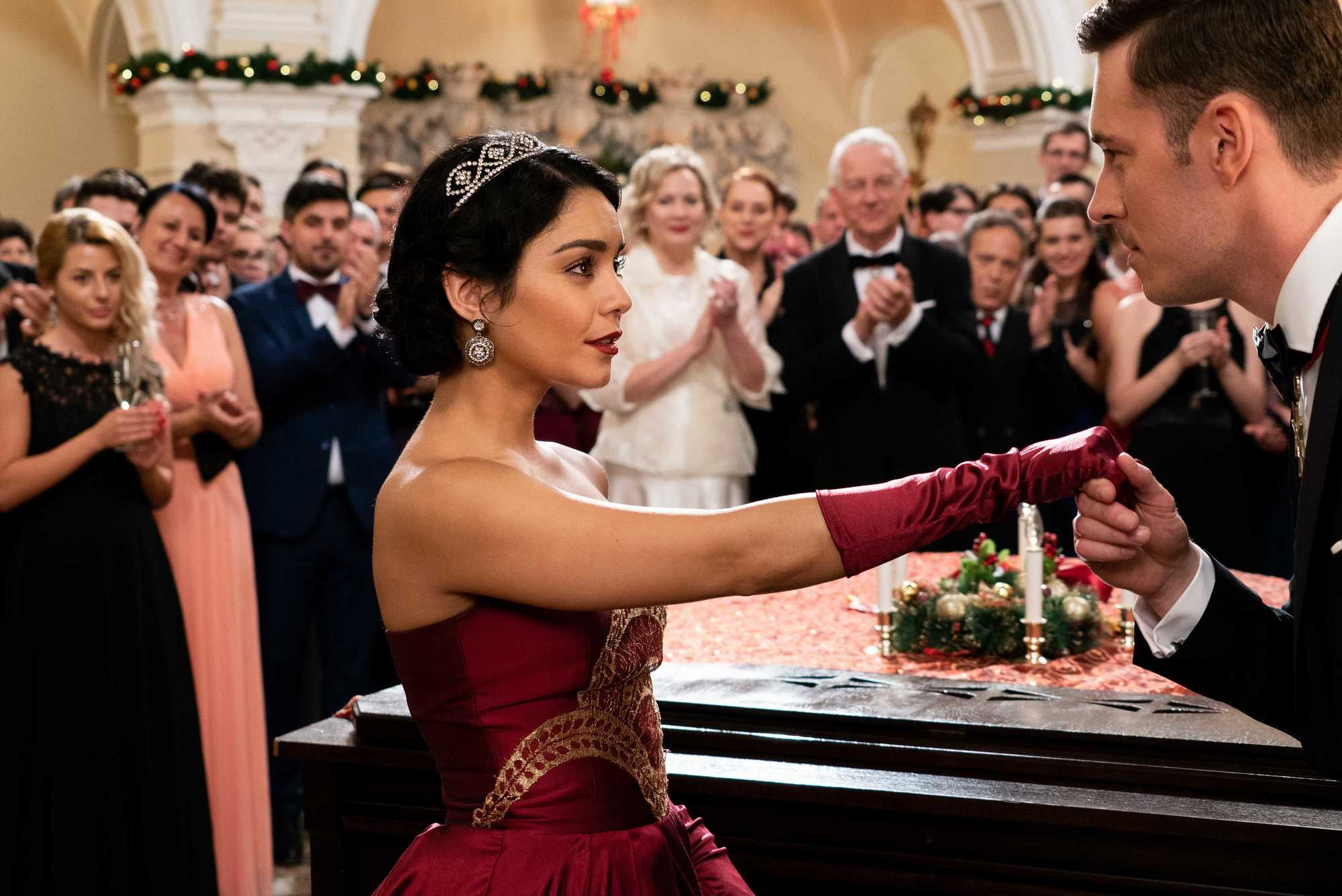 The Princess Switch: Vanessa Hudgens as Stacey De Novo on set, wearing a red gown with her black hair styled into a low sleek bun with a tiara, surrounded by people
