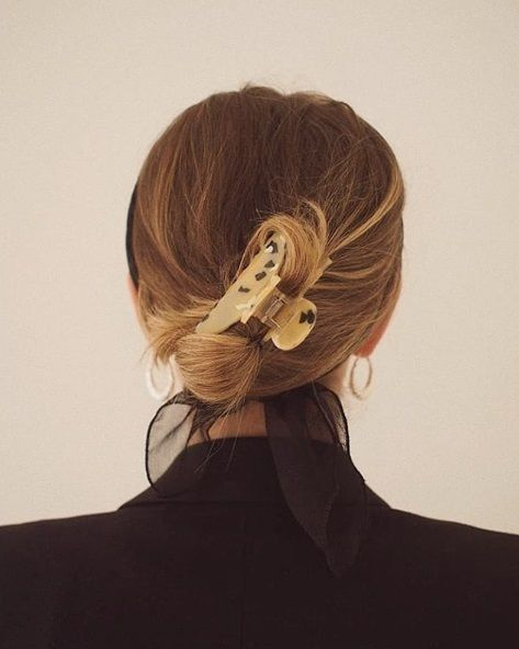 Updos for thin hair: Back view of a woman with light brown and blonde highlighted hair in a messy updo with a tortoiseshell claw clip