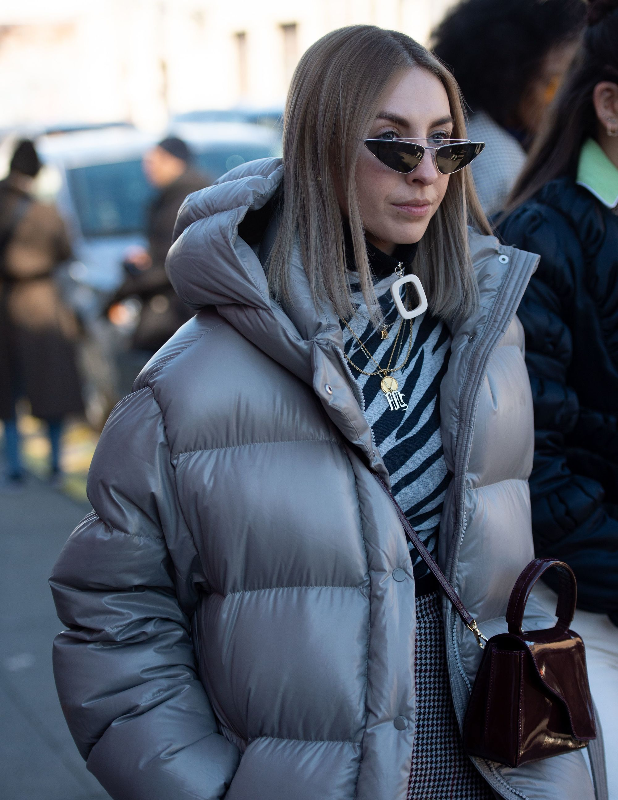 Woman with shoulder length dark brown hair with ash blonde ombre, wearing a grey puffer jacket with micro glasses outside