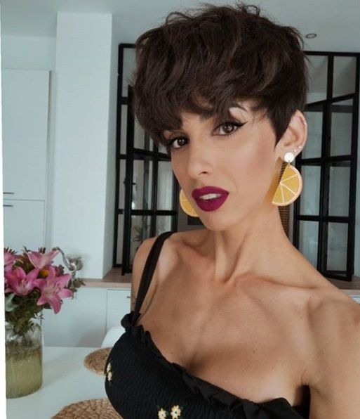 Brunette woman with a short curly pixie cut