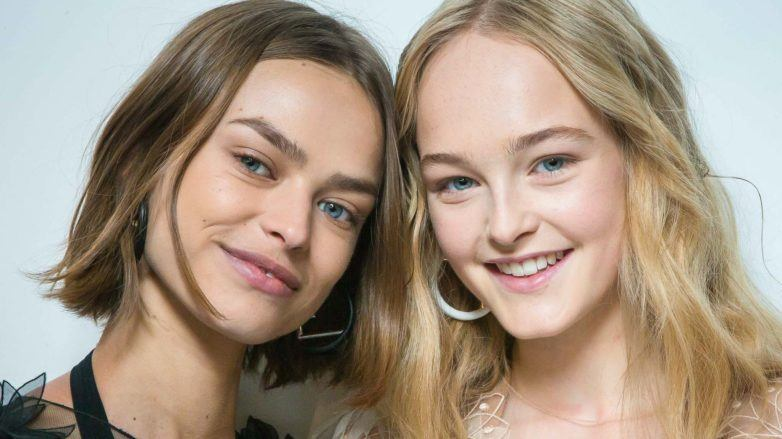 Flexible hold hairspray: Shot of two models with tousled, natural-looking waves, backstage, one with short light brown hair and the other with golden blonde hair