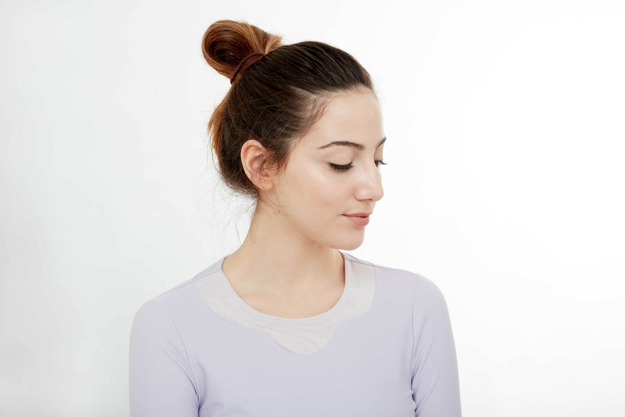 Gym hairstyles for thick hair: Brunette model with long hair tied in a looped bun, wearing a lilac gym top