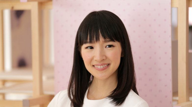 How to Marie Kondo your hair products: Shot of Marie Kondo with her dark medium hair and blunt bangs, wearing a white top and posing against a pink studio background