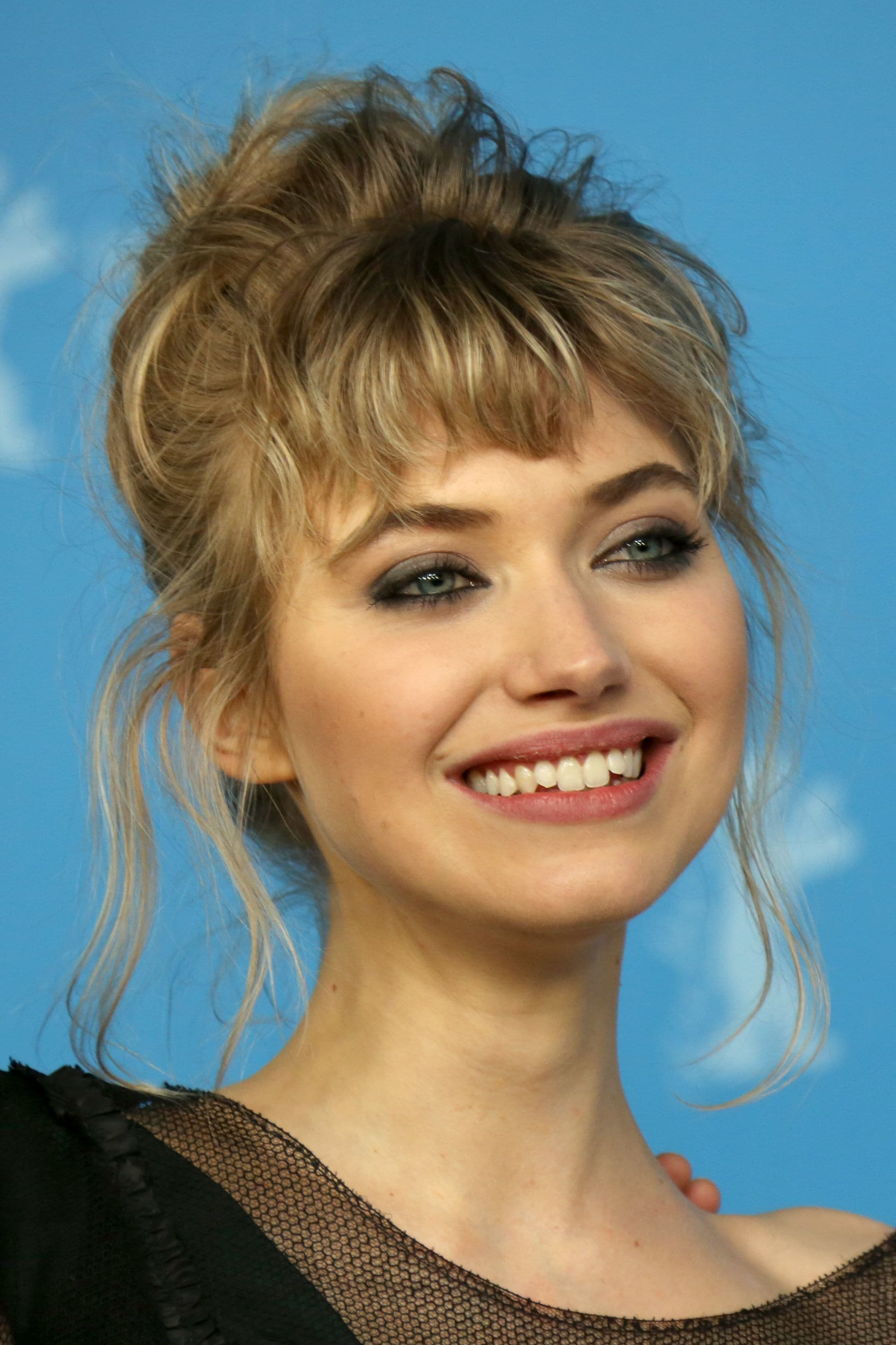 Micro fringe: Imogen Poots with wavy dirty blonde hair and micro fringe styles in a messy bun smiling.