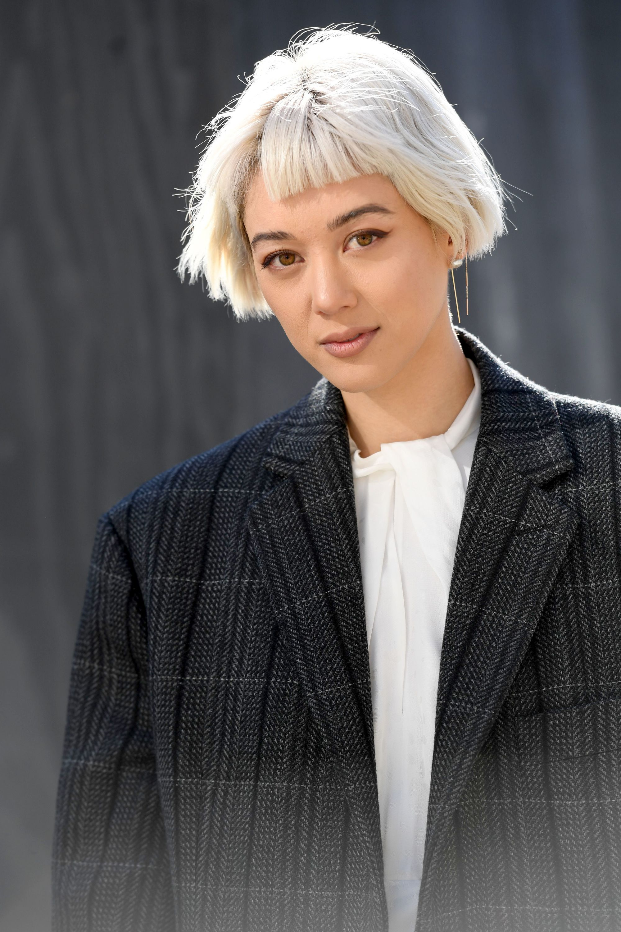 Woman with bright ash blonde bob with micro fringe, wearing a black blazer with white shirt