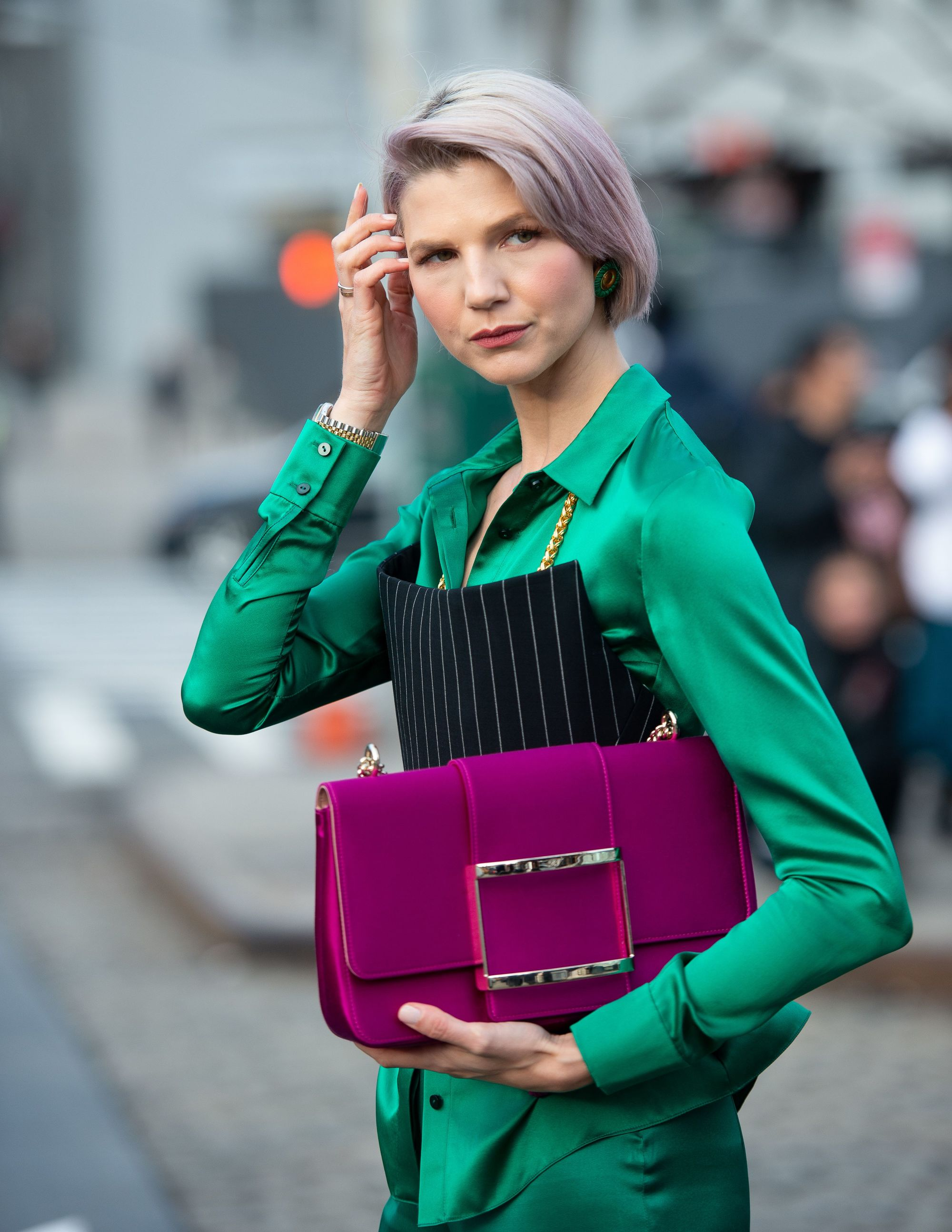 Woman with chin length ash blonde bob with lilac wash, wearing an emerald green suit and holding a purple bag outside