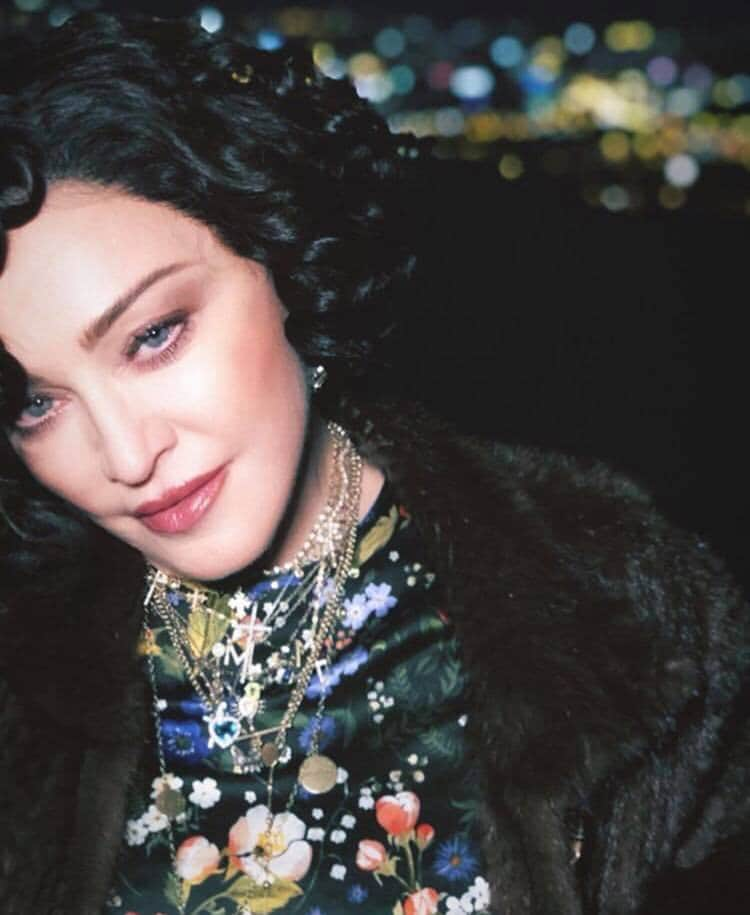 Close up shot of Madonna with dark hair, with retro curls, wearing a floral top and fur coat with necklaces posing for photo