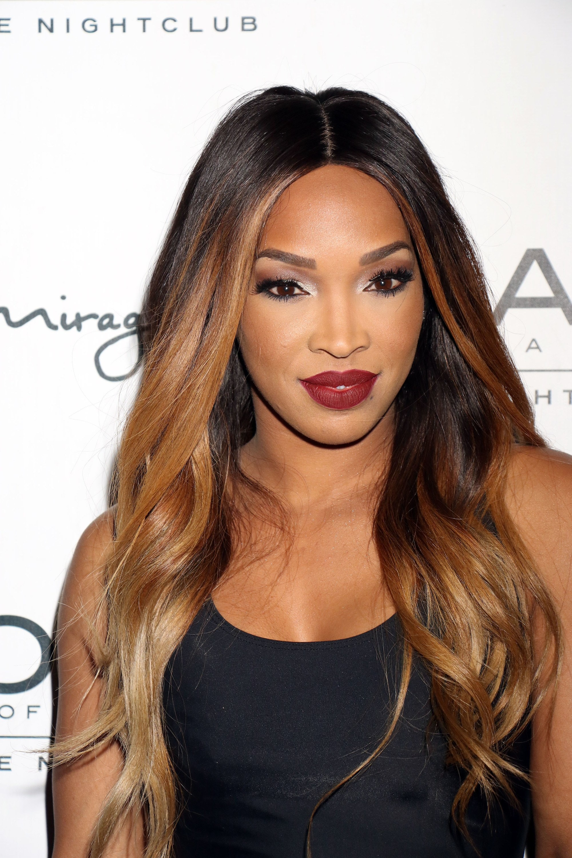 Brown hair with blonde highlights: Malika Haqq with long dark hair with caramel face-framing highlights