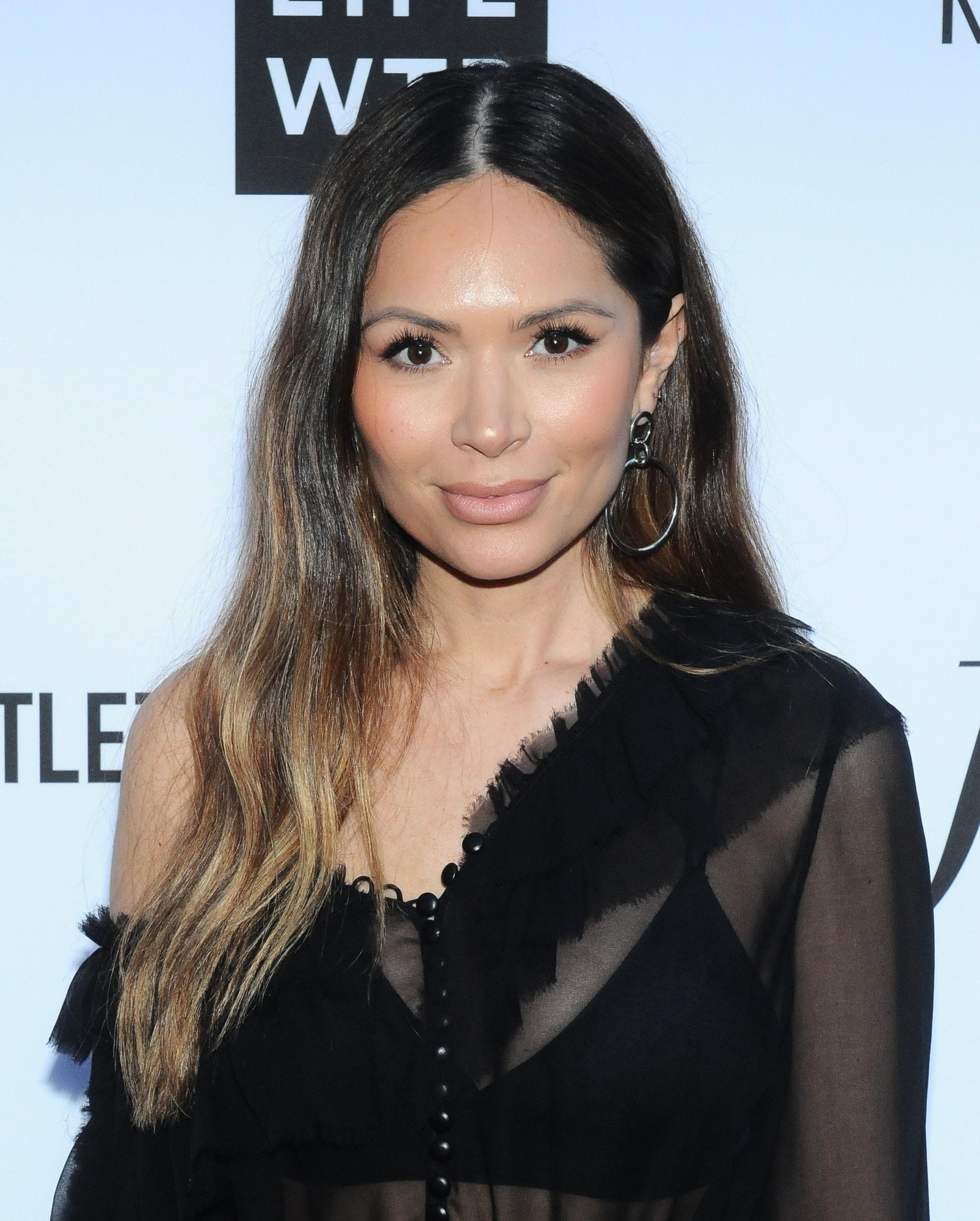 Brown hair with blonde highlights: Marianna Hewitt with long wavy brown hair with blonde highlights, wearing a sheer black top