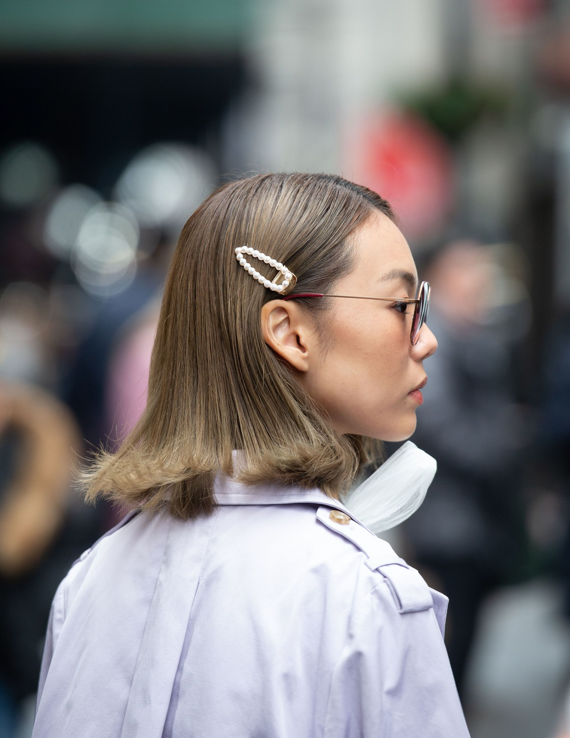 Ash blonde hair: Side shot of woman with medium ash blonde straight bob with pearl hair clip on the street