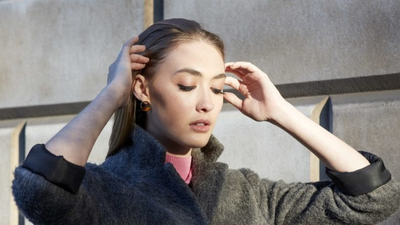My hair is thinning: Street style shot of a model with slicked back brunette hair touching her hair with her hands, wearing a grey coat outside