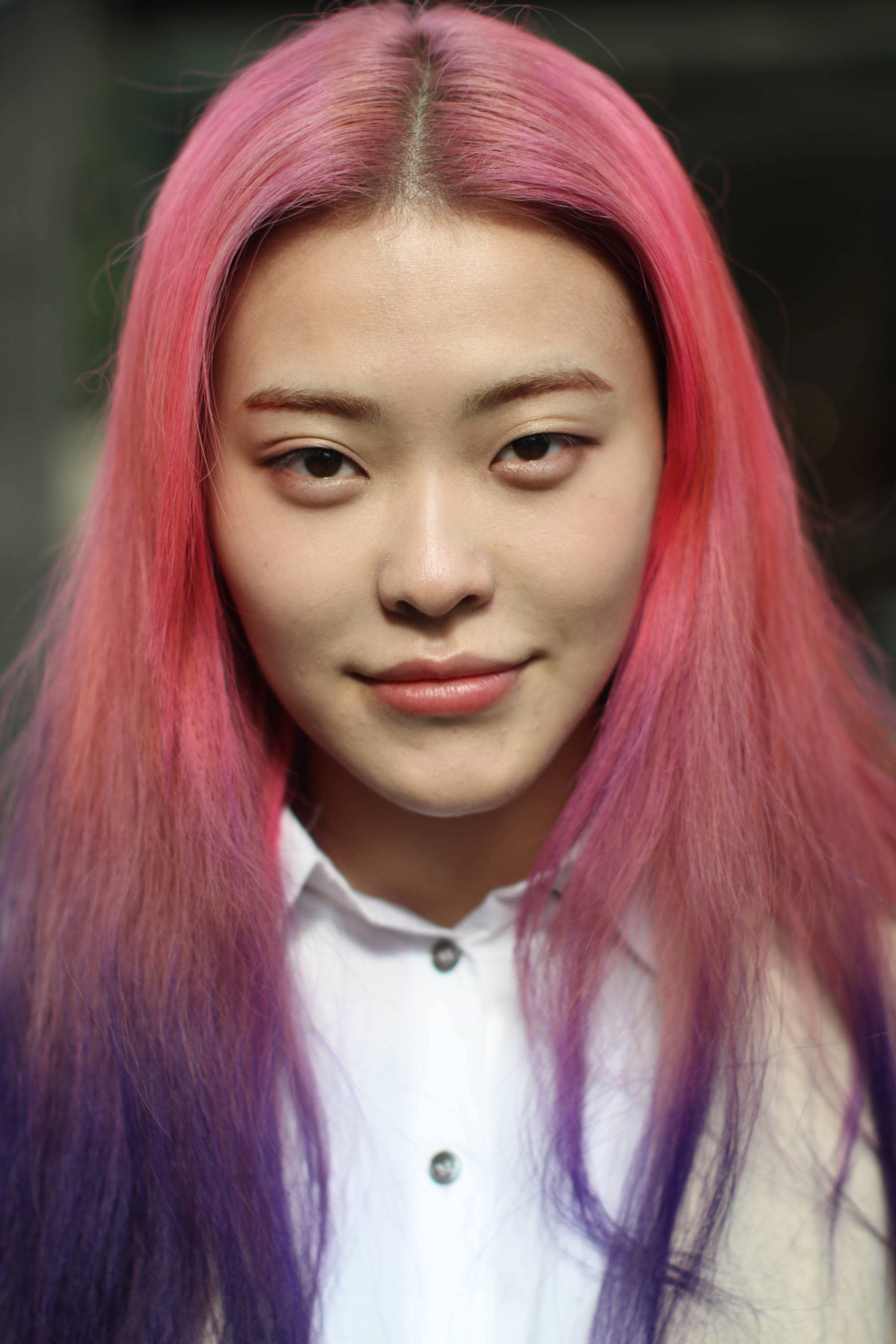 Pink ombre hair: Close-up headshot of a street styler with straight long pink to purple ombre hair, wearing a white shirt