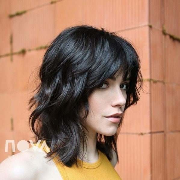 Woman with dark brown hair with a layered shag cut