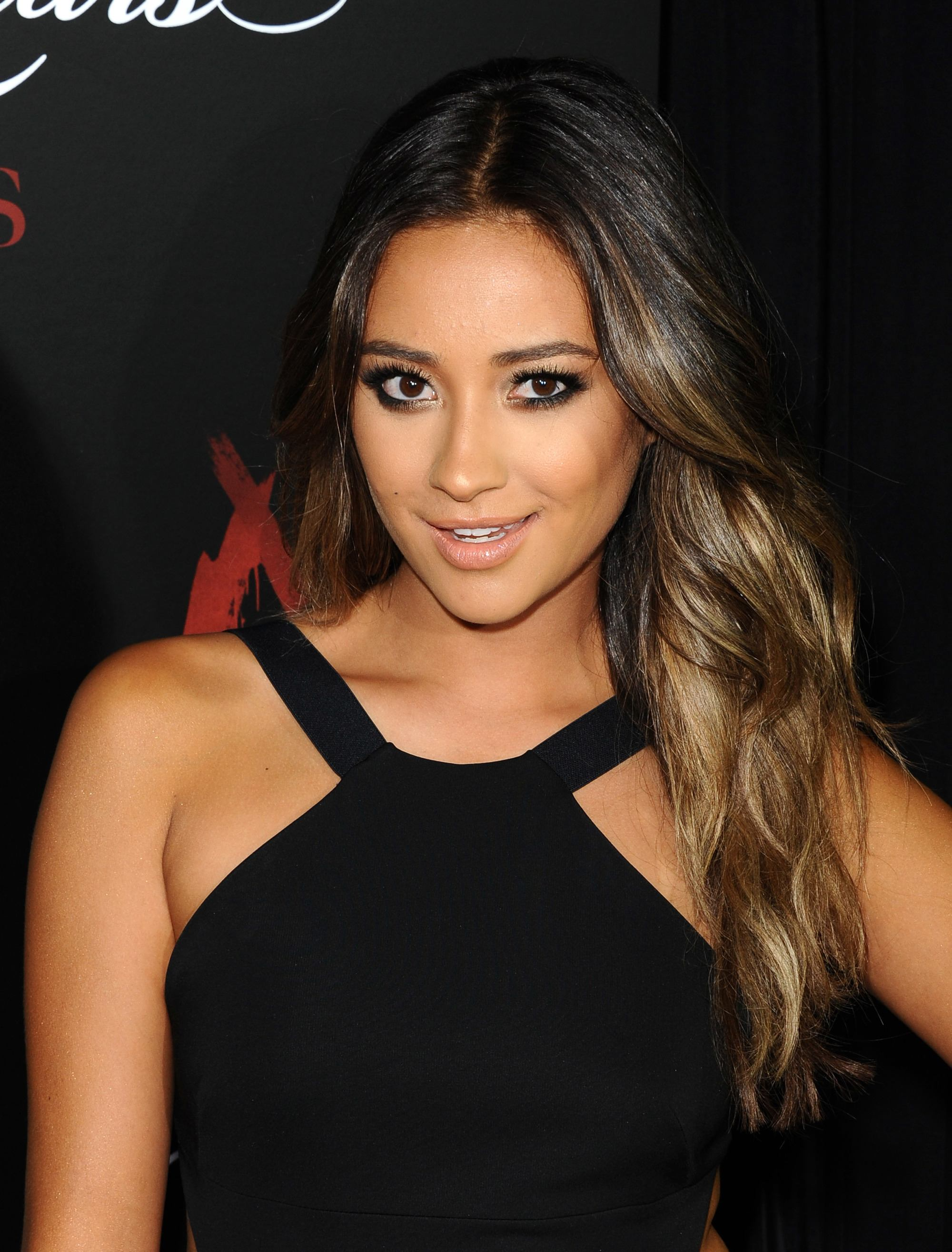 Brown hair with blonde highlights: Shay Mitchell with dark brown hair with highlights, worn in loose curls and swept over one shoulder