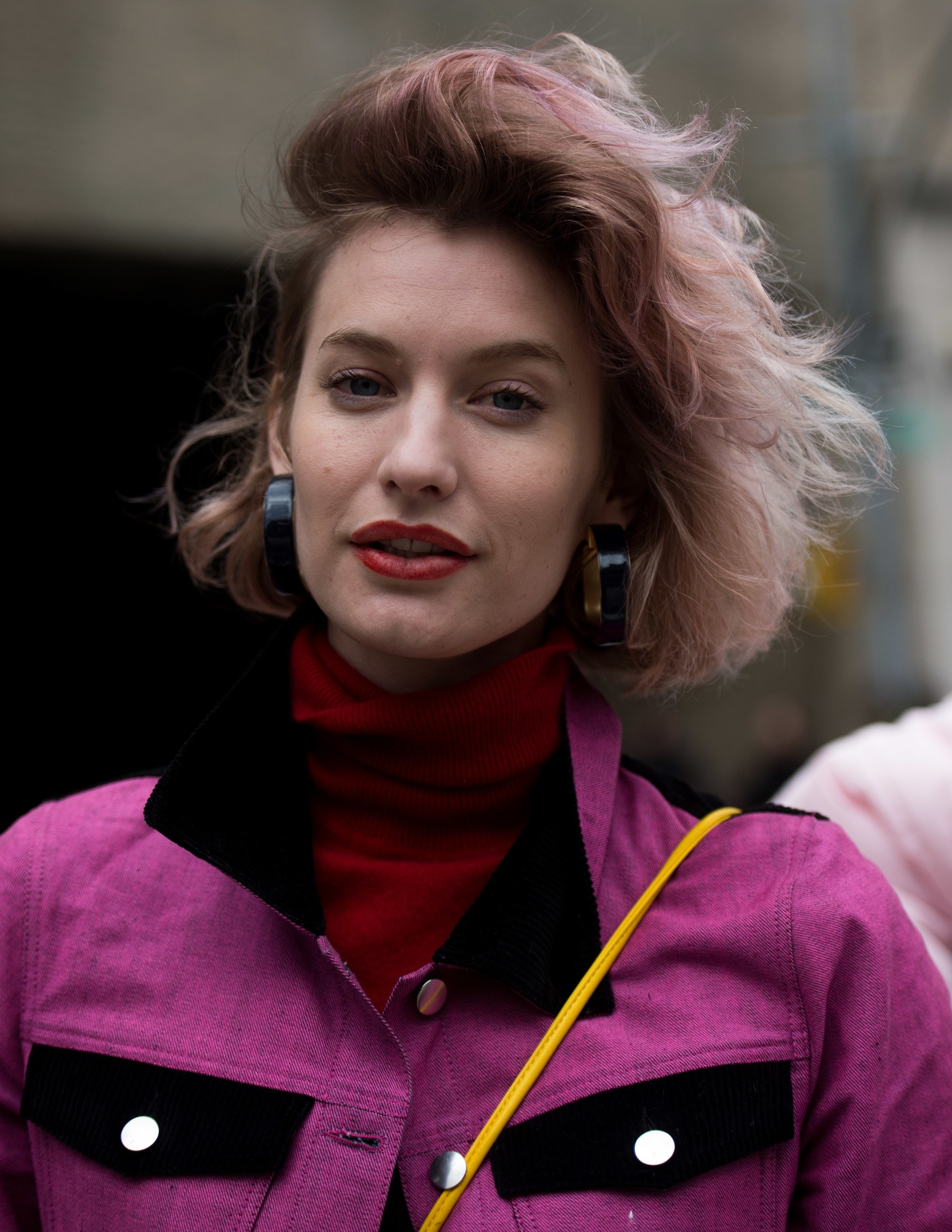 Pink ombre hair: Street style shot of a woman with light brown and pink ombre hair, wearing a red roll neck top and a pink jacket