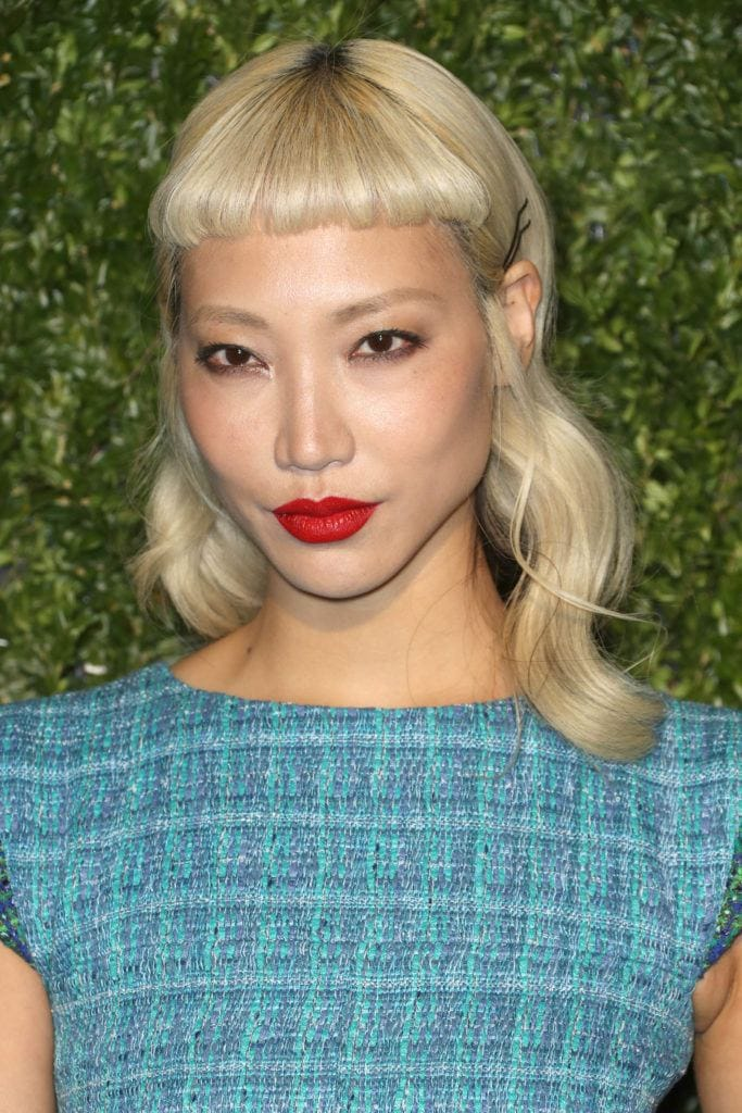 Micro fringe: Soo Joo Park with bleach blonde shoulder length hair in retro waves with a micro fringe wearing a bold red lipstick.