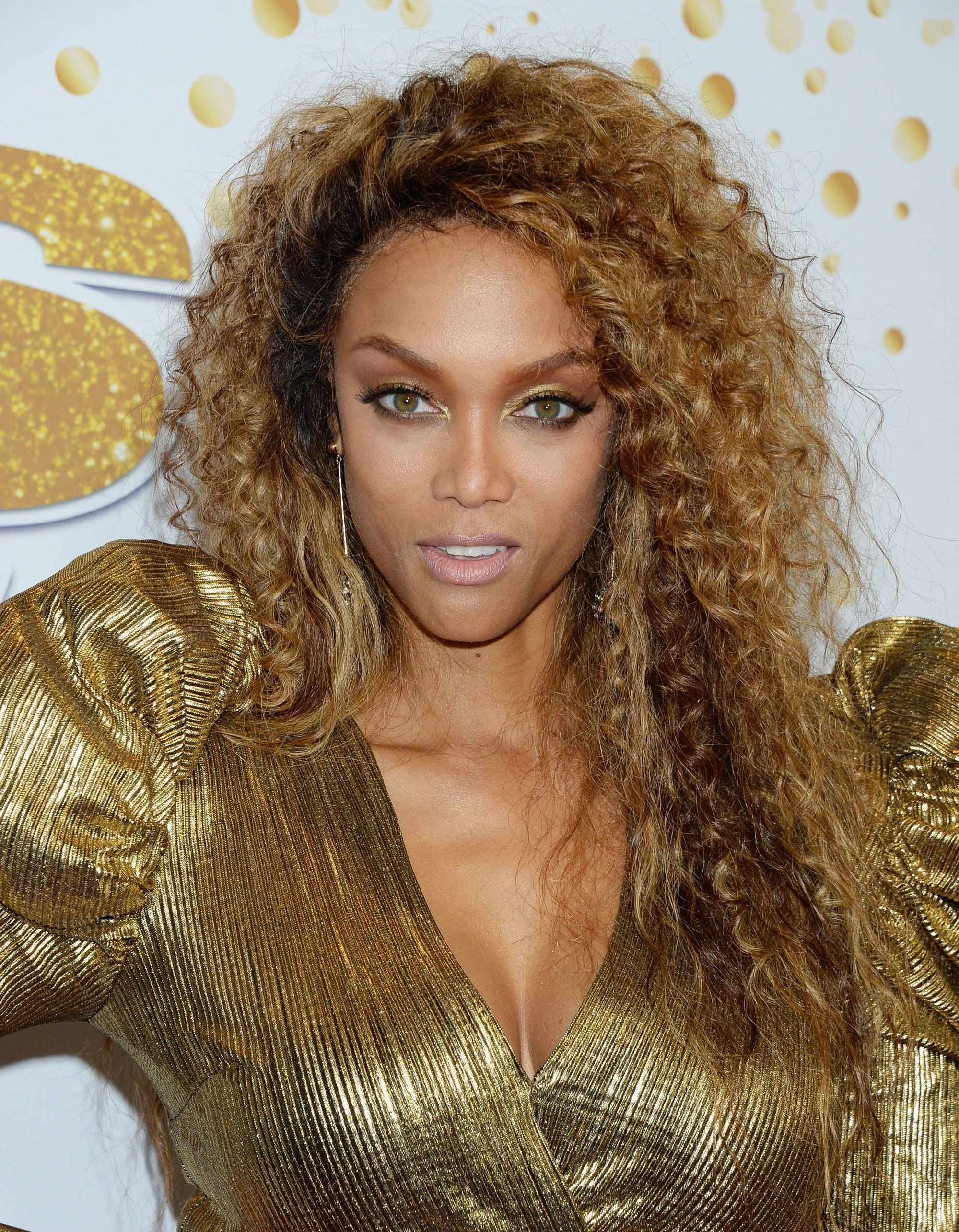 Brown hair with blonde highlights: Tyra Banks with long curly golden brown highlighted hair, wearing a gold metallic dress