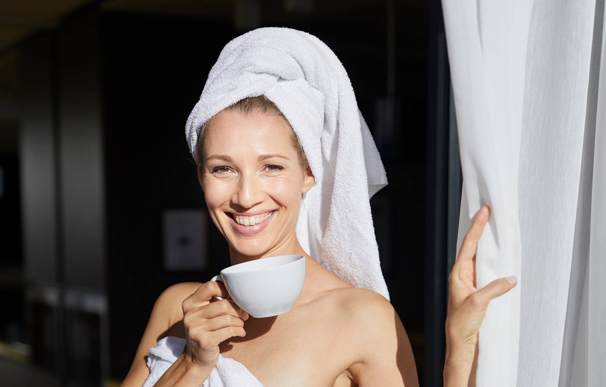 Valentine's Day pamper guide: Woman with her hair wrapped in a towel, wearing a white towel and holding a cup of tea