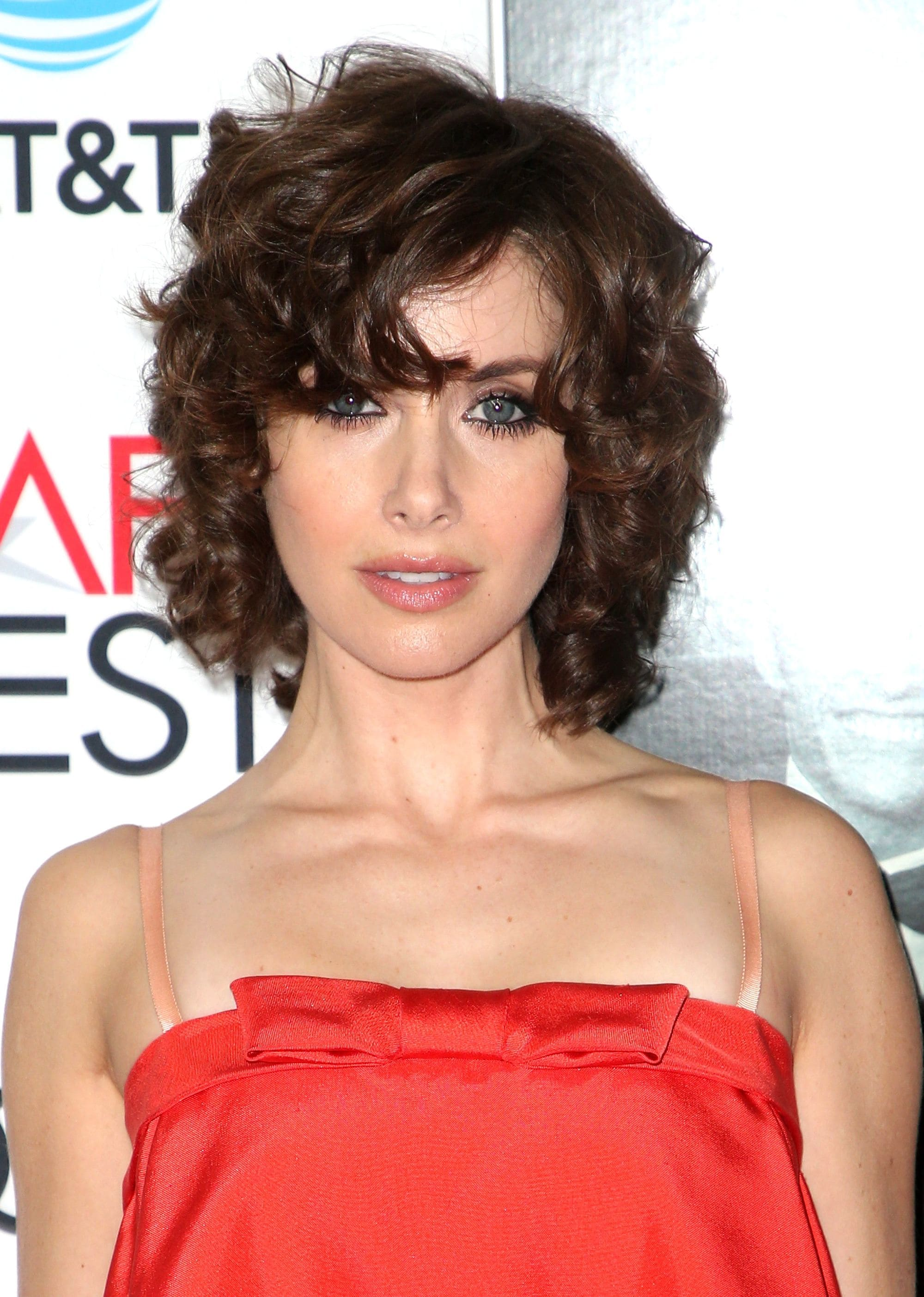 Bob hairstyles: Alison Brie with cropped curly bob hair, wearing red strapless dress on the red carpet