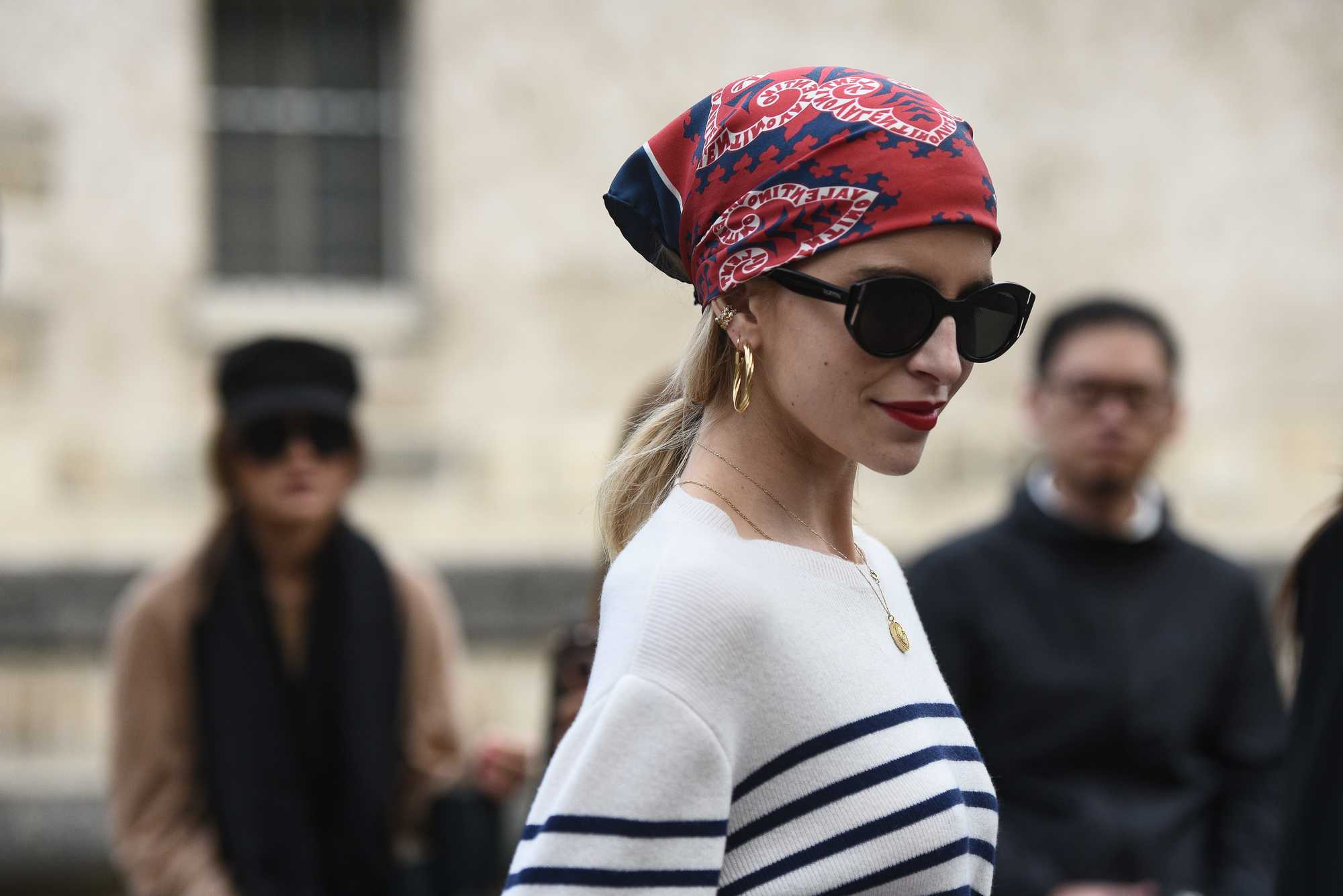 Bandana hairstyles: Woman with bandana wrapped around her head, wearing sunglasses and posing on the street