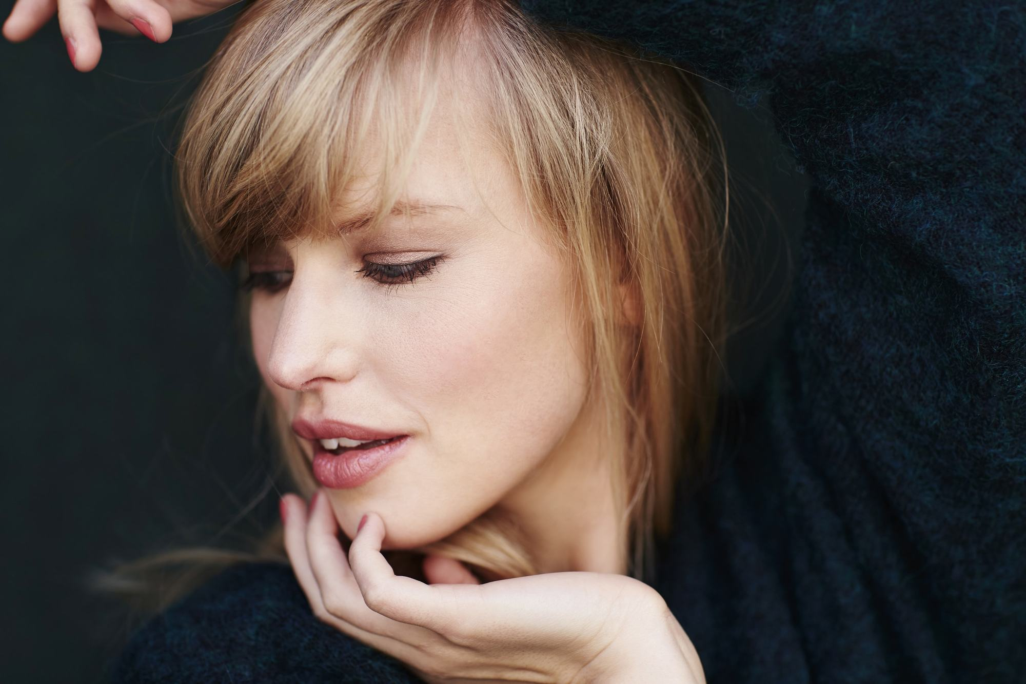 Blonde woman with a fringe hair cut looking down holding her face