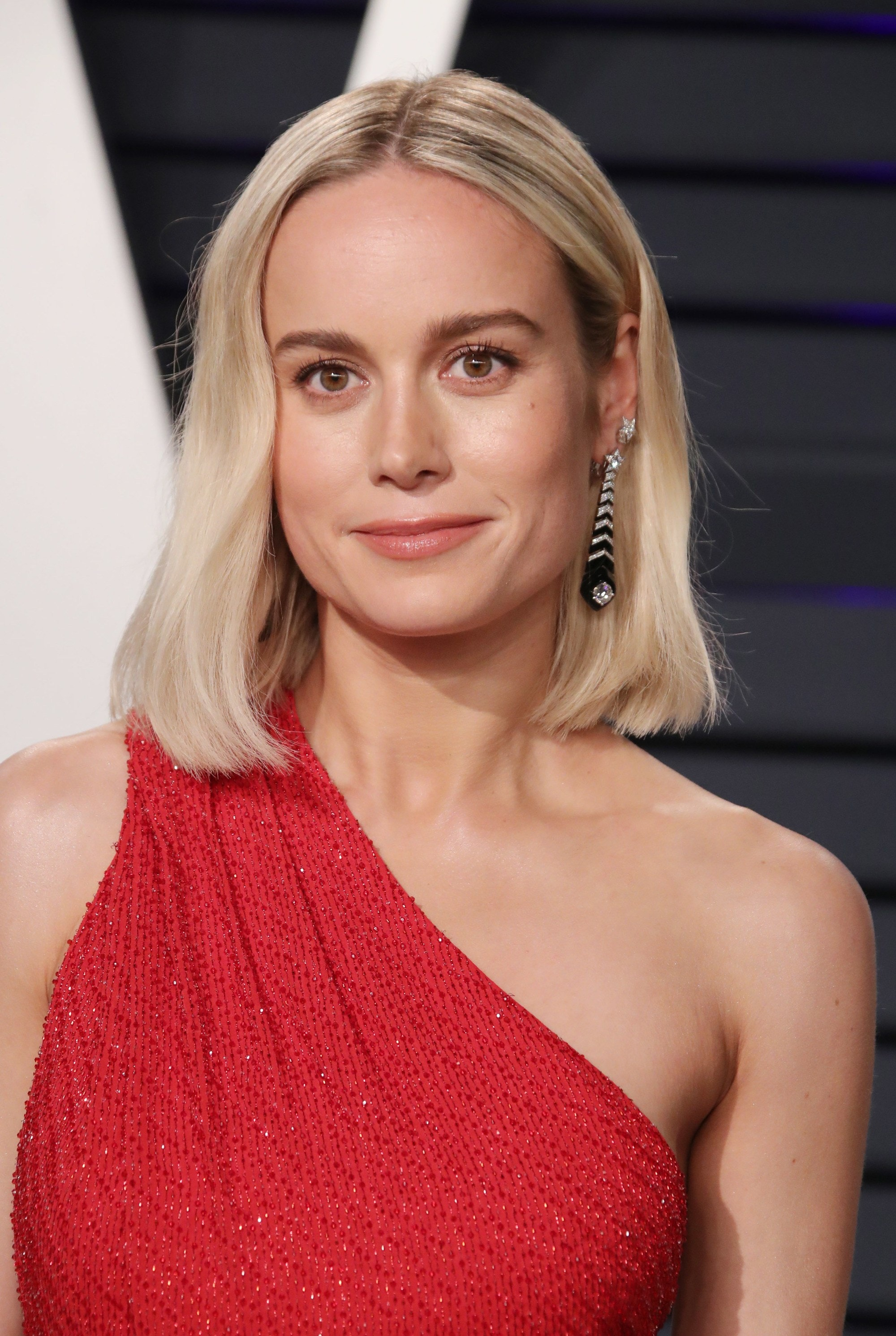 Bob hairstyles: Bie Larson with platinum blonde long wavy bob wearing red dress on the red carpet