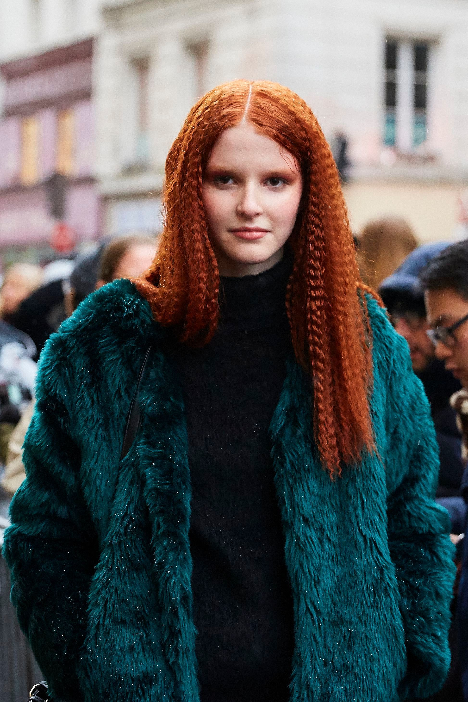 Crimped hair: Street style shot of a redhead woman with long crimped hair, wearing a teal fur coat