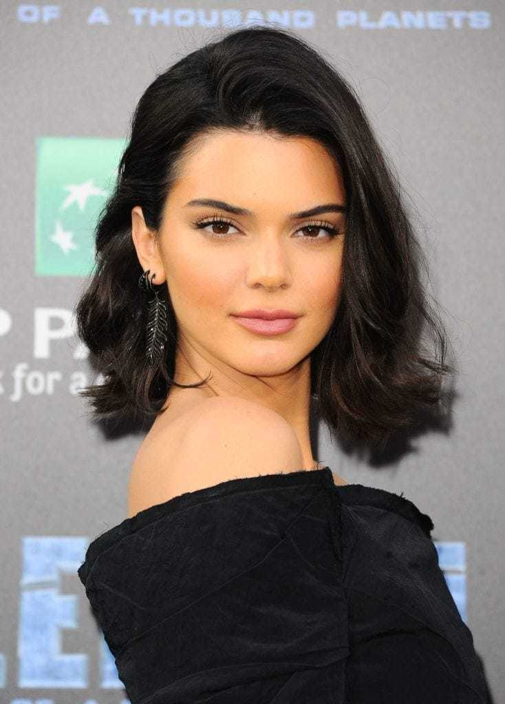 Bob hairstyles: Kendall Jenner with a long dark brown swoop bang haircut, wearing black on the red carpet