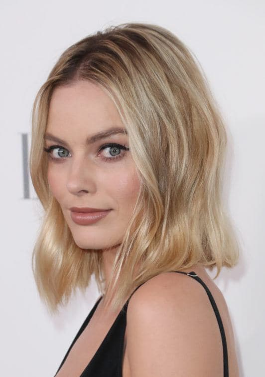 Margot Robbie with long wavy beach bob hair, wearing a dark strappy top on the red carpet