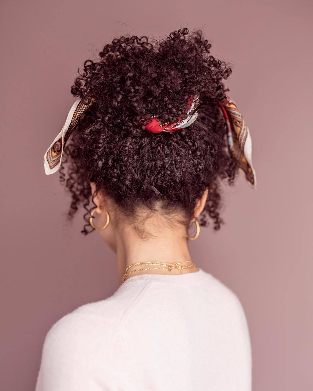 Bandana hairstyles: Woman with natural curly brown hair styled into a pineapple with bandana around it