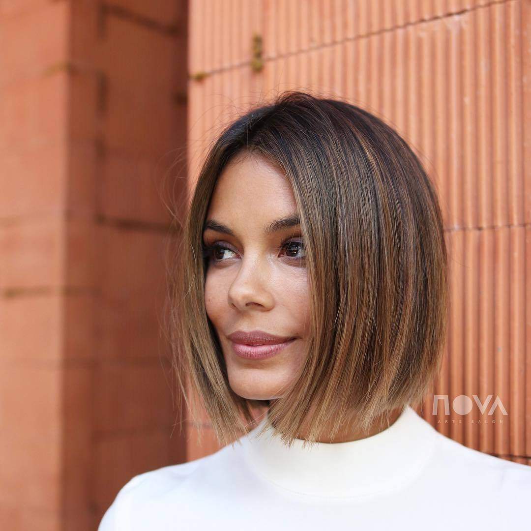 Caramel highlights: Woman with bobbed dark brown hair with caramel highlights, wearing white and posing outside